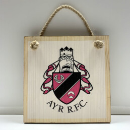 square wooden plaque with ayr rugby club logo and rope